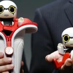 In this Sept. 27, 2016 photo, Toyota Motor Corp. SMO Moritaka Yoshida, right, and Fuminori Kataoka, project general manager from Toyota Motor Corp., pose for photographers with compact sized humanoid communication robots, Kirobo Mini, during a press unveiling in Tokyo. The new robot from Japanese automaker Toyota Motor Corp. can't do much else but chatter in a high-pitched voice. (AP Photo/Shizuo Kambayashi)