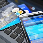 Mobile banking, financial success, accounting and electronic internet money payments business concept: macro view of stack of credit cards and modern touchscreen smartphone on office laptop keyboard with selective focus effect